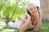 Woman wearing headphones while lying on the lawn