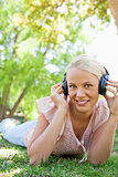 Smiling woman with headphones enjoying music on the grass