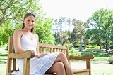 Smiling woman enjoying her day on a bench in the park