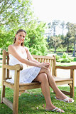 Smiling woman with her legs crossed  sitting on a park bench