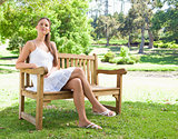 Woman with her legs crossed sitting on a bench
