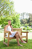 Smiling woman with her legs crossed sitting on a bench