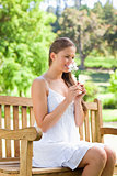 Smiling woman smelling on a flower while sitting on a park bench