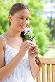 Smiling woman on a park bench smelling on a flower