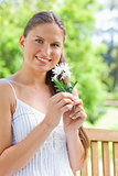 Smiling woman with a flower sitting on a bench