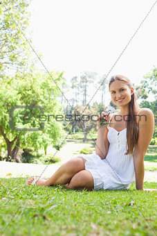 Smiling woman sitting on the grass in a park