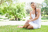 Smiling woman sitting on the lawn in the park