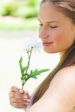 Close up of a woman smelling a flower