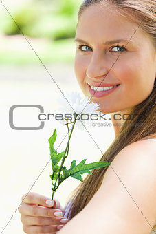 Close up of a smiling woman smelling a flower