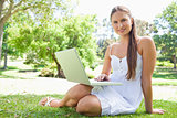 Smiling woman with s laptop on the lawn