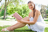 Side view of a smiling woman sitting on the lawn with a book