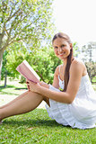 Side view of a smiling woman sitting on the grass with a book