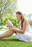 Side view of a woman reading a book on the grass