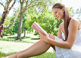 Side view of a woman sitting on the lawn while reading a book