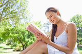 Side view of a smiling woman on the lawn reading a book