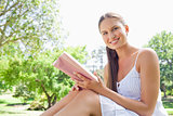 Side view of a smiling woman with a book on the lawn