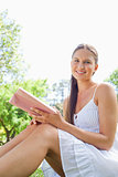 Side view of a smiling woman sitting in the park with a book