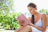 Side view of a woman reading a novel in the park