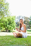 Smiling woman on the grass with her tablet computer