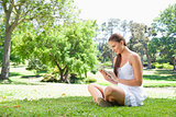 Side view of woman on the lawn with her tablet computer