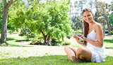 Smiling woman using her tablet computer on the lawn