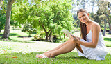 Smiling woman with her tablet on the lawn