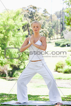 Relaxed woman doing yoga exercises in the park