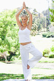 Smiling woman doing yoga exercises outdoors