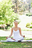 Smiling woman sitting in a yoga position in the park