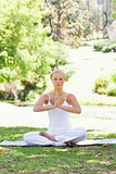 Woman sitting in the park in a yoga position