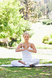 Woman in a yoga position sitting on the lawn