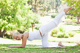 Side view of a woman doing gymnastic exercises in the park