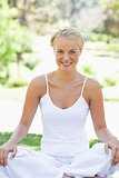 Smiling woman in a yoga position on the lawn