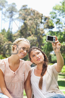 Woman taking a picture of herself and a friend