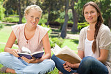 Students sitting in the park with their books