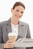 Smiling businesswoman holding newspaper and cup