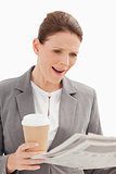 surprised businesswoman reading newspaper