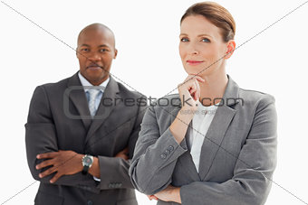 Smiling businessman behind businesswoman rests head on hand