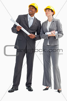 Businessman and woman with notes and hard hats