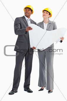 Businessman and woman wearing hard hats holding paper looking up