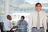 Smiling young businessman leans on table