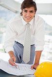 Smiling businessman with blueprints and a hard hat