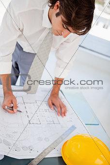 Man working hard on blueprints for work