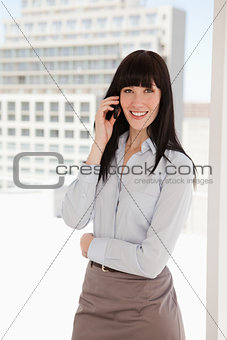 A smiling woman in a suit making a call on her mobile