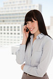 Smiling woman in the office talking on a mobile