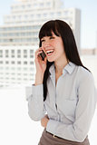 Woman laughing on her phone in the office