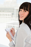 A woman looking back at the camera as she holds a notepad