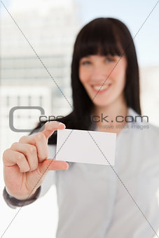 Focus on the business card with a woman holding it