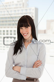 A woman with her arms crossed over and smiling