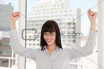 A smiling happy woman with her arms raised just above her head